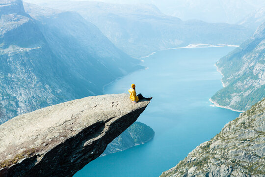 a girl in a yellow seats on the Trolltunga in Norway