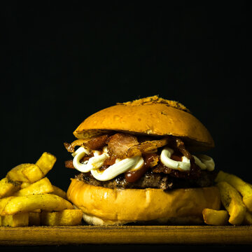 Tasty Fresh Home Made Gourmet Burger With Fries on Wooden Table With Dark Background