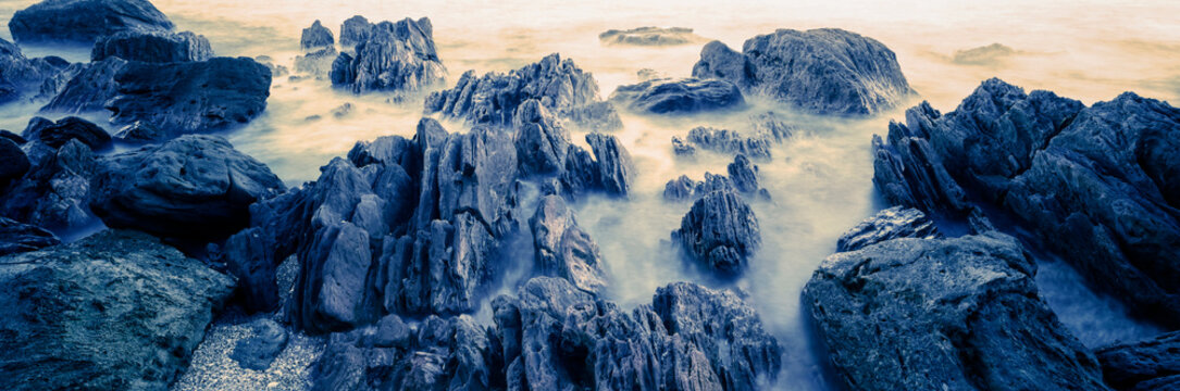 Misty waves rolling in around rocks on rocky beach
