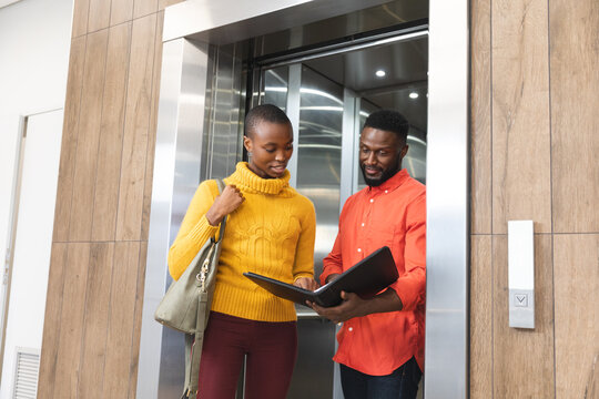 Smiling african american male and female creative colleagues holding notes, talking at elevator