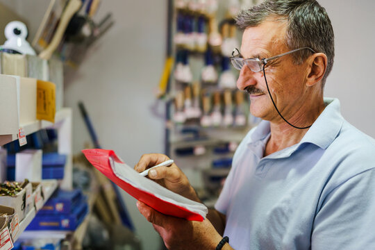 Side view portrait of adult senior caucasian man standing at his store real people small business entrepreneur holding folder with documents checking goods and delivery orders