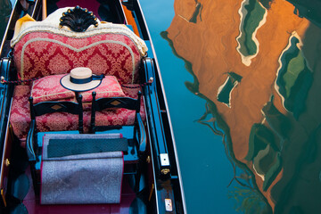Beautiful gondola with a soft seat in the peaceful water with a reflection of a building in Venice