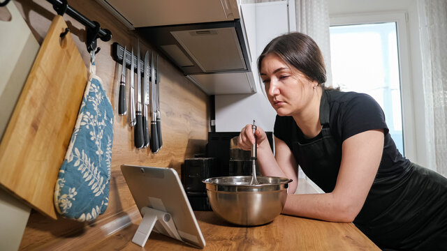 brunette woman mixes with a whisk and looks into a tablet in kitchen.