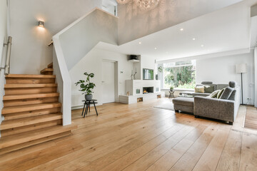 Fototapeta Cozy house interior with a wooden floor, large gray sofa, and stairs leading to the second floor obraz