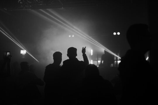 Black and White photo of People pointing and dancing to a DJ with lights in a nightclub.