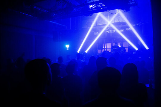 People dancing to a DJ with blue lights in a nightclub.