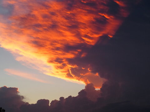 Thunderstorm at sunset produced deep red colors on the underside of the cumulonimbus anvil.