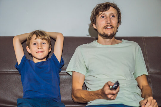 Father and son watching TV in evening at home