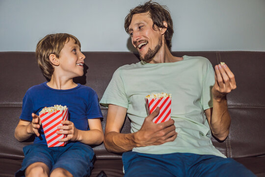 Father and son watching TV and eat popcort in evening at home