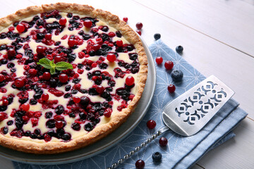 Delicious currant pie and fresh berries on white wooden table