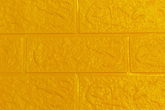 The yellow gold  wallpaper texture has an abstract roughness and brick wall pattern for the background.