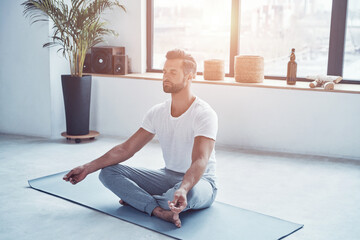 Totally relaxed young man doing yoga while sitting in lotus position at home