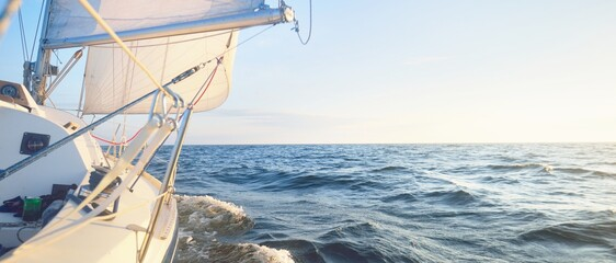 Sailing in the cockpit of a yacht in an open sea at sunrise. Clear blue sky, warm sunlight. Waves...