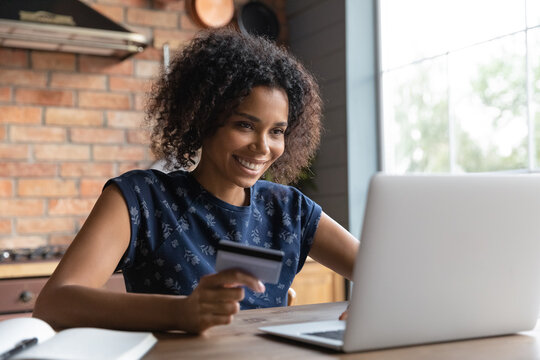 Happy millennial female shopper using laptop and credit card at home. Young African American woman shopping on internet stores, paying bills, loan fees, making payment for online purchases. Ecommerce