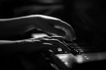Pianist's fingers on a keyboard in black and white