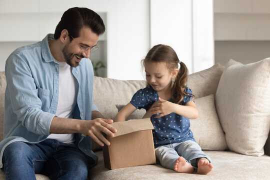 Happy dad and excited daughter girl unboxing parcel with surprising gift, opening cardboard box, looking inside container, producing goods. Father and kid receiving purchase via delivery service
