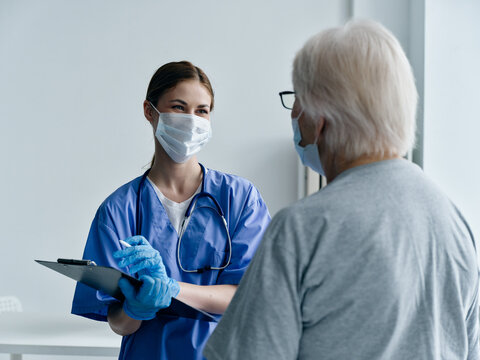 woman nurse in medical mask with documents in hands looking at elderly woman patient cropped view covid-19 passport