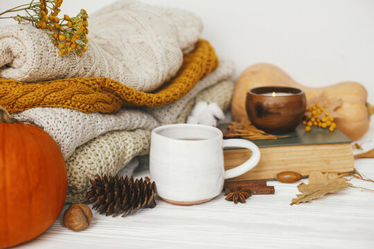 Hello autumn, cozy slow living. Pumpkin, cup of tea, cozy sweaters, autumn leaves, burning candle and vintage book on white wooden background in room. Happy Thanksgiving