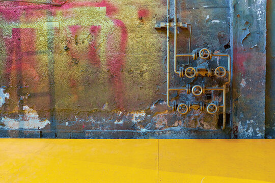 Colorful dirty wall with industrial pipe taps and vivid blue, red, yellow, green colors and flaking plaster texture for backgrounds