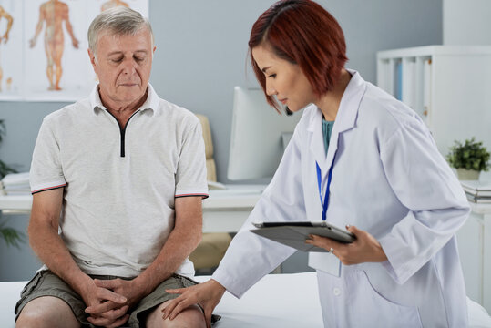 Physiotherapist with tablet computer in hands touching knee of senior patient who had bad injury
