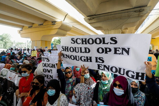 Teachers of private schools hold signs during a protest demanding the opening of schools, which are closed amid the coronavirus disease (COVID-19) pandemic, in Karachi