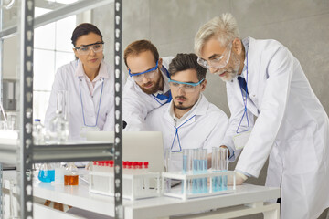 Portrait of a team of scientists working in a modern medical research laboratory. Concentrated serious colleagues discuss and analyze research with a laptop. Concept of science, technology and people