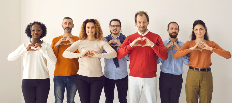 Studio group portrait of thankful youth and senior citizens sending you love, support and gratitude. Team of young and mature people doing heart shape hand gesture isolated on white banner background