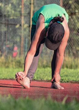 Female athlete doing Preventive exercises against cramps a