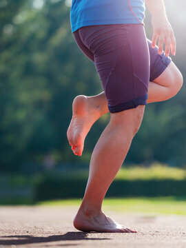 Forthy yeas old woman stretching legs before run during sunny morning