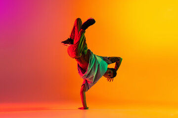 Portrait of young stylish man, break dancing dancer training in casual clothes isolated over gradient pink yellow background at dance hall in neon light.
