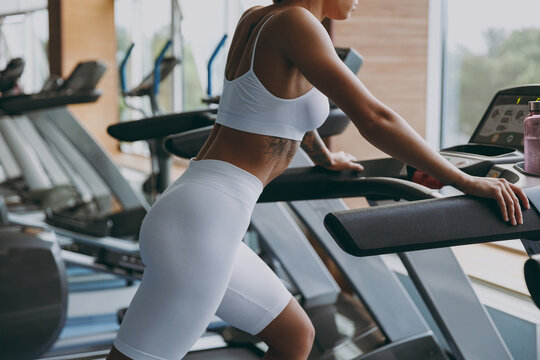 Cropped up photo shot side profile view young strong sporty athletic sportswoman woman 20s wearing white sportswear warm up training run on treadmill in gym indoors Workout sport motivation concept