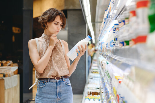 Young minded woman 20s in casual clothes backpack shopping at supermaket store buy choose dairy produce take milk read shelf life prop up chin inside hypermarket. Purchasing gastronomy food concept