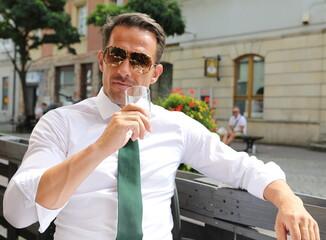 Fototapeta Bardzo przystojny, elegancki mężczyzna w białej koszuli i zielonym krawacie i okularach przeciwsłonecznych. obraz