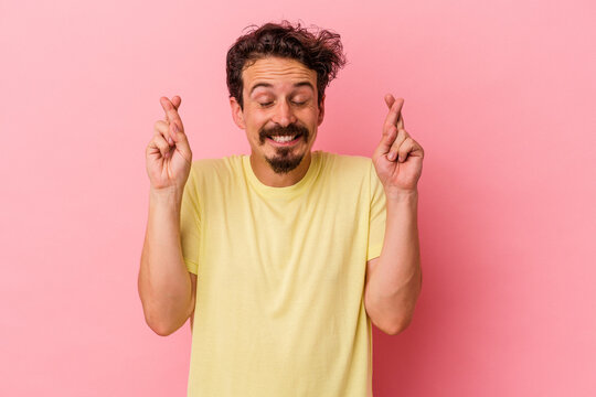 Young caucasian man isolated on pink background crossing fingers for having luck