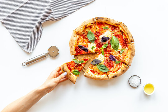 Female hands hold slice of pizza. Overhead view