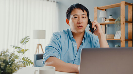 Freelance Asia guy casual wear using laptop talk on cell phone in living room at house. Working...
