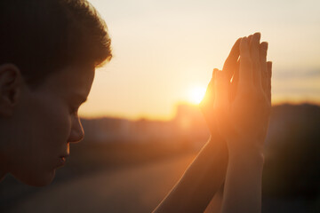 Fototapeta Hands of young christian woman praying at sunrise light, religion and spirituality concept obraz