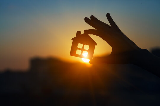 Man holding  wooden house model against sunset light for sale or rent, family home and shelter concept, real estate, solar energy and eco accommodation