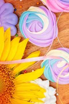 Assorted colorful meringues and sunflowers on a wooden background