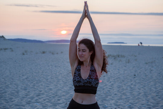 young woman practicing yoga and meditating on the beach