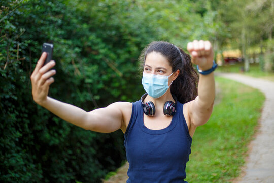 A young caucasian woman wearing a mask with headphones and smartphones taking selfie