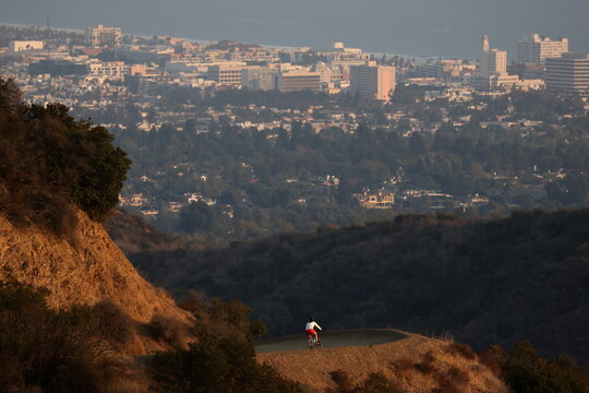 A cyclist rounds a corner on a hiking trail overlooking the Pacific Ocean in Los Angeles