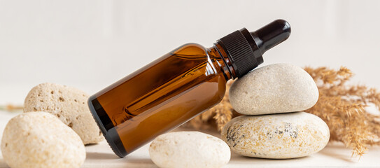 Obraz Side view composition with dark glass dropper bottle wit essential oil and stones and dry reeds. home spa and skin care concept - fototapety do salonu