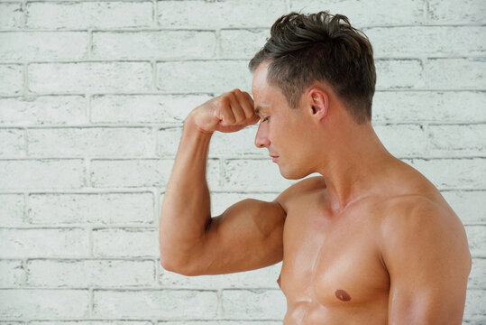 Shirtless strong fit young man flexing biceps muscles