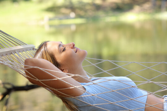 Profile of a woman resting on hammock beside a lake