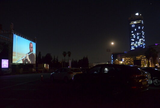 People sit in their cars for an outdoor screening during the International Film Festival in Amman