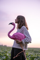 Carefree woman with pink flamingo on potato field in the evening, enjoying sunset and purple sky