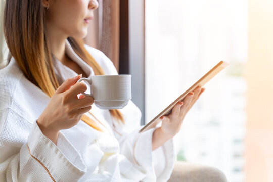 Asian woman wearing a bathrobe drinking coffee after wake up and using digital tablet in bedroom