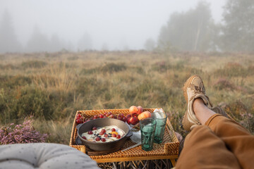 Woman having a picnic and enjoying great view on nature in foggy weather, sitting relaxed in the vehicle trunk, view from a car interior
