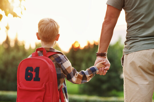 Little son schoolboy with backpack holding hand of father dad while going to first grade in school